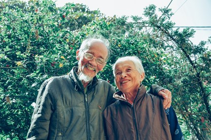 Elderly couple standing in front holly bush